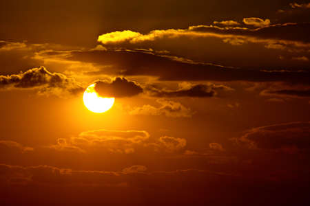 Sunset sky with clouds and sun photo