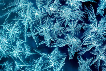 hoar: Frost formations on a window with dark background