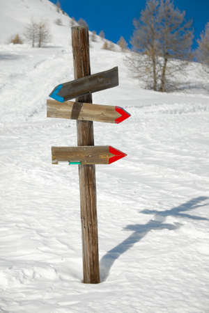 Directional sign post on the snow photo