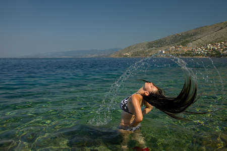Woman splashing water in the sea photo