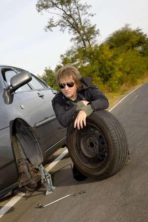 break down: Man changing tires on car