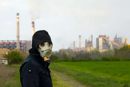 Man in gas mask near a high pollution metal factory photo