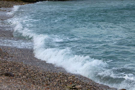 dull: Waves hitting the shore in dull weather Stock Photo