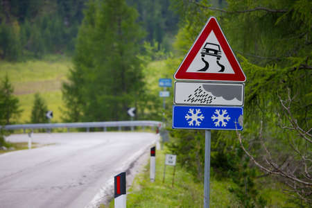 slippery: Mountain road with warning sign Stock Photo