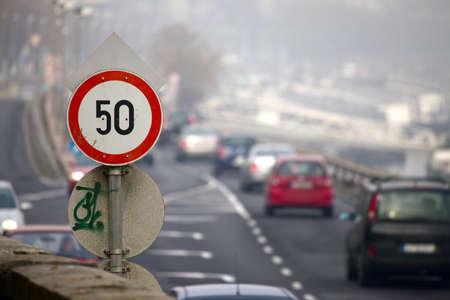 limits: Speed limit traffic sign on a busy urban road