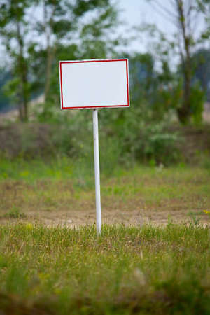 Empty signboard on a green field photo