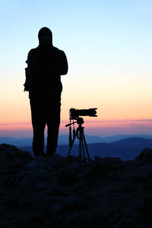 telephoto: Silhouette of a landscape photographer in twilight Stock Photo
