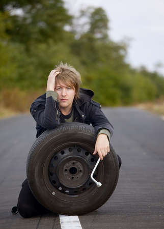 puncture: Man with wheel on the road
