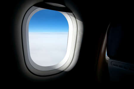 Plane window with bright blue sky photo