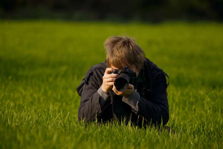 to crouch: Photographer shooting on a field Stock Photo