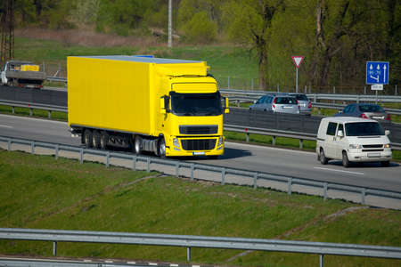 Yellow truck transporting cargo on the highway