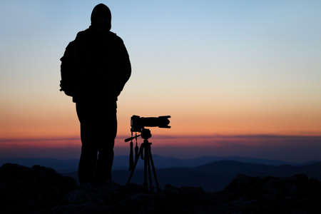 Silhouette of a photographer with his camera on a hilltop photo