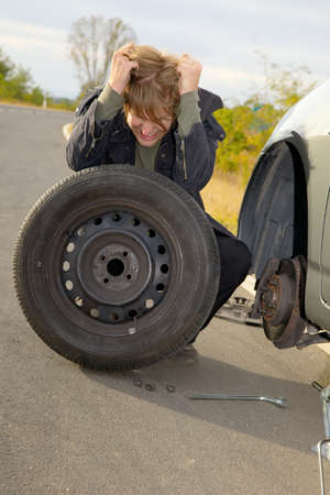 winter tyre: Frustrated man changing wheel on a car