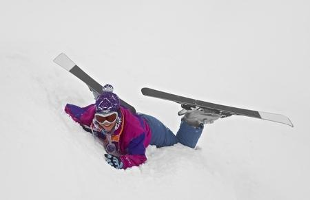 Female skier fallen in deep snow