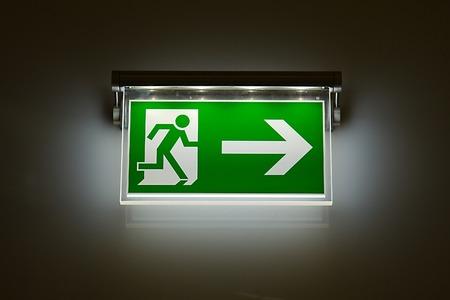 Panneau de sortie d'urgence rougeoyante dans le noir Banque d'images - 28581375