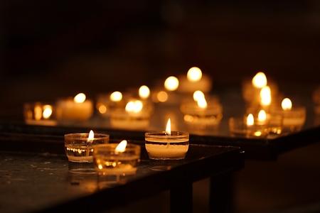 Rijen van brandende kaarsen in een dim kerk Stockfoto