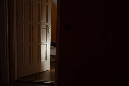 Light coming from a room with door left ajar Imagens