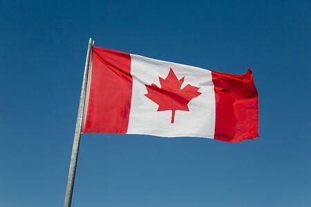 Canadian flag waving against blue sky