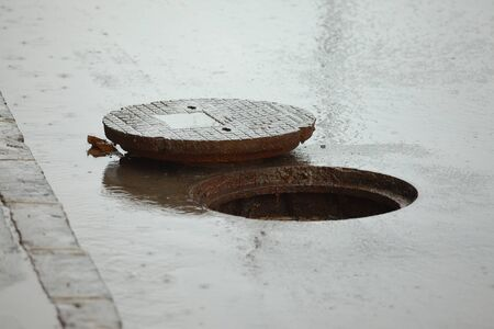 Sewer cover open on a rainy street Imagens