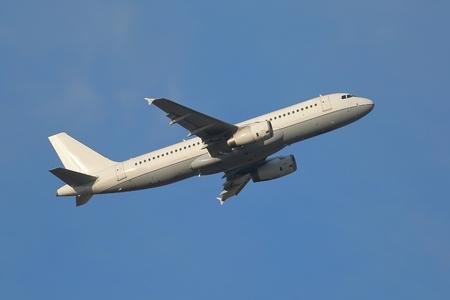 Vliegtuig vliegt weg naar de blauwe hemel
