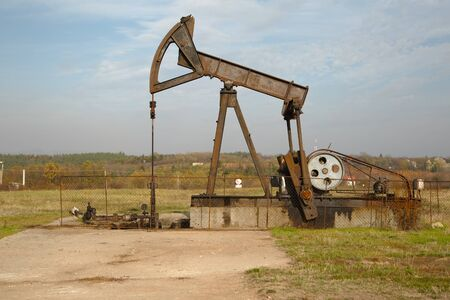 Old rusty oil well on a field
