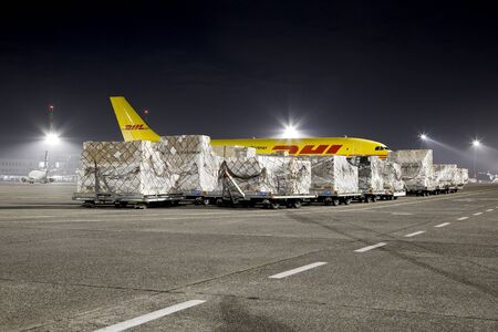BUDAPEST, HUNGARY - MARCH 5, 2014: DHL Airbus A300 cargo plane at Budapest Airport with containers to be loaded. DHL is a world market leader in air mail