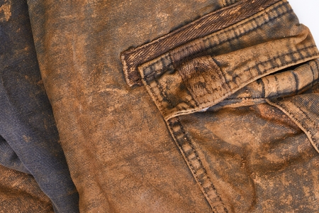 Torn and dirty working trousers covered in mud and clay, back side
