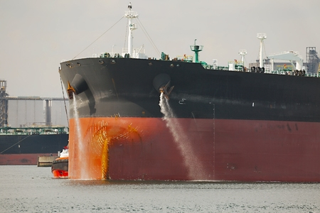 Large crude oil tanker ship pumping out ballast water when coming into port