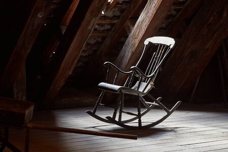Old rocking chair on a dim attic window light