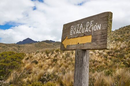 Emergency evacuation route sign in Spanish language at volcano Cotopaxi showing the way to move up to escape pyroclastic flow in case of eruption. The text reads Evacuation route in Spanish.
