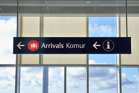 Arrivals sign at an airport in English and Icelandic. Komur translates to arrivals. Фото со стока