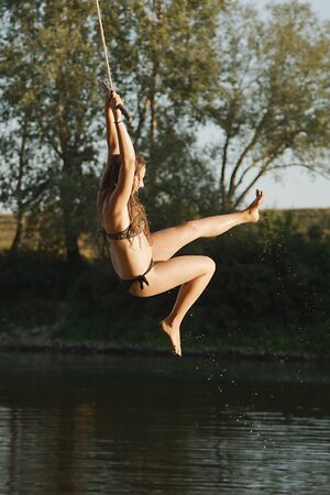 Young woman on a rope swing by the river