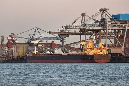 Industrial harbor with rusty structures, bulk carrier ship