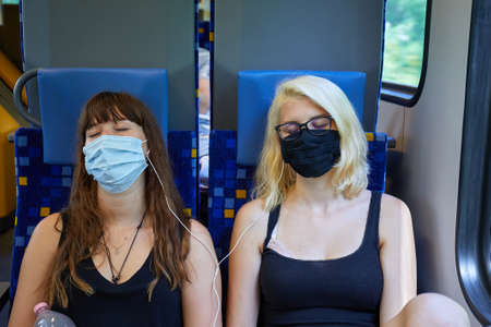 Young women on a train wearing masks