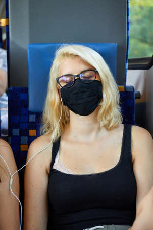 Young woman on a train wearing masks Stock fotó