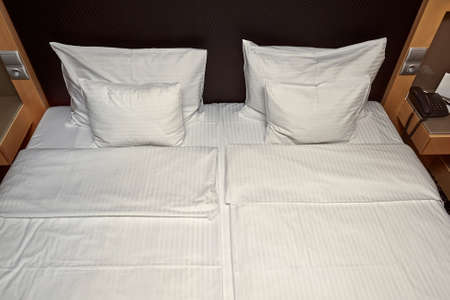 Hotel bed with white sheets Фото со стока