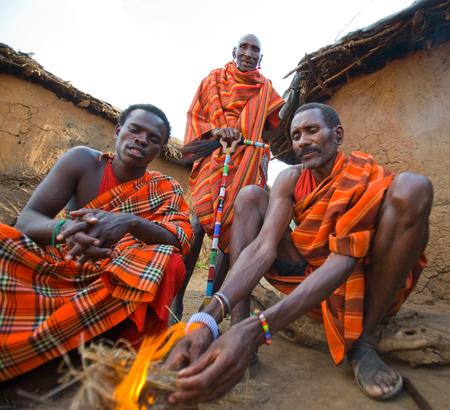 masai mara: KENYA, MASAI MARA - JULY 19, 2011: Men Masai tribe make a fire in the traditional way. Editorial