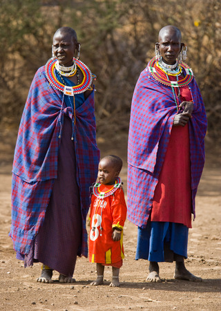 masai mara: KENYA, MASAI MARA - JULY 19, 2011: Maasai women are standing at the gates of Maasai village.