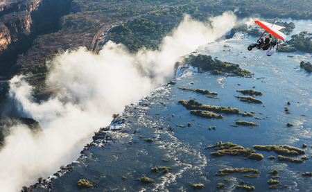 ZAMBIA, VICTORIA FALLS, AFRICA - 18 JULY: Tourists fly over the Victoria Falls on the trikes. Editorial