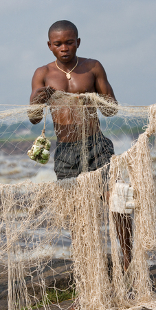 REPUBLIC OF CONGO, SUBURB OF BRAZZAVILLE - MAY 09, 2007: Young men catch fish on the bank of the river of Congo.