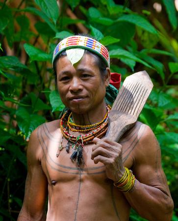 MENTAWAI PEOPLE, WEST SUMATRA, SIBERUT ISLAND, INDONESIA - 16 NOVEMBER 2010: Portrait of a man Mentawai tribe in traditional headdress.