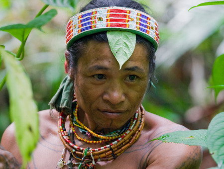 MENTAWAI PEOPLE, WEST SUMATRA, SIBERUT ISLAND, INDONESIA - 16 NOVEMBER 2010: Portrait of a man Mentawai tribe in traditional headdress.
