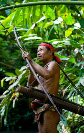 MENTAWAI PEOPLE, WEST SUMATRA, SIBERUT ISLAND, INDONESIA - 16 NOVEMBER 2010: Man hunter Mentawai tribe with a bow and arrow in the jungle. Editorial