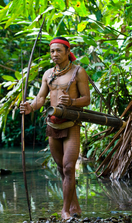 MENTAWAI PEOPLE, WEST SUMATRA, SIBERUT ISLAND, INDONESIA - 16 NOVEMBER 2010: Man hunter Mentawai tribe with a bow and arrow in the jungle. 에디토리얼