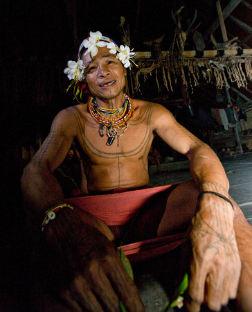 MENTAWAI PEOPLE, WEST SUMATRA, SIBERUT ISLAND, INDONESIA - 16 NOVEMBER 2010: Mentawai tribe man sitting in a traditional house on the floor.