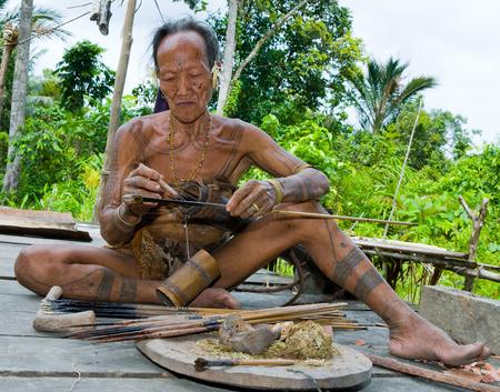 MENTAWAI PEOPLE, WEST SUMATRA, SIBERUT ISLAND, INDONESIA - 16 NOVEMBER 2010: Men Mentawai tribe prepare arrows for hunting.