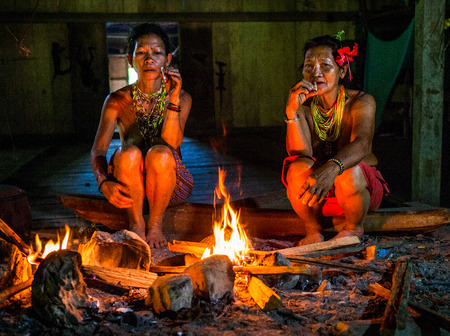 MENTAWAI PEOPLE, WEST SUMATRA, SIBERUT ISLAND, INDONESIA - 03 OKTOBER 2011: Two women Mentawai tribe sitting around the campfire in a traditional house. Editorial
