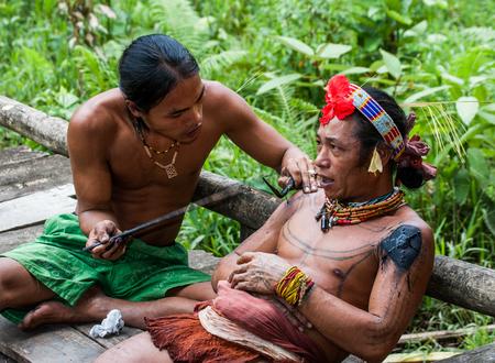 MENTAWAI PEOPLE, WEST SUMATRA, SIBERUT ISLAND, INDONESIA - 03 OKTOBER 2011: Men Mentawai tribe make tattoo.