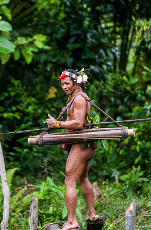 ancients: MENTAWAI PEOPLE, WEST SUMATRA, SIBERUT ISLAND, INDONESIA - 16 NOVEMBER 2010: Man hunter Mentawai tribe with a bow and arrow in the jungle. Editorial