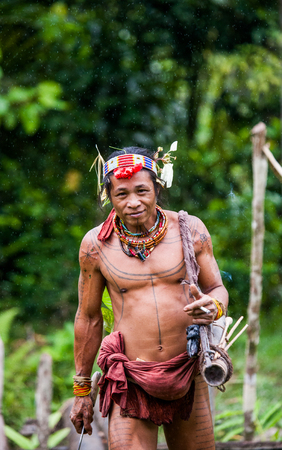 MENTAWAI PEOPLE, WEST SUMATRA, SIBERUT ISLAND, INDONESIA - 16 NOVEMBER 2010: Man hunter Mentawai tribe with a bow and arrow in the jungle. Editoriali